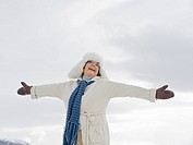 A senior woman wearing a fur hat with arms outstretched