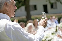 A senior man raising a champagne glass at a wedding