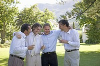 A group of men drinking champagne at an outdoor wedding reception