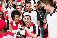 Man in crowd catching ball at football match