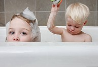 Little girl and boy in bathtub.