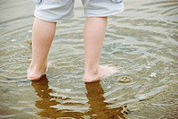 A picture of a young boy's legs as he plays in a puddle on the beach