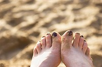 Sandy toes with painted toenails on a beach