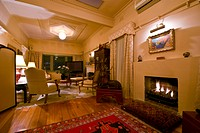 A fire warms a living room decorated in Art Deco furnishings.