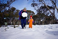 A father and son gather a snowball to use as a head on a snowman.