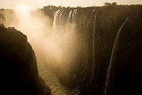 Sunlight illuminates mist rising from Victoria Falls.