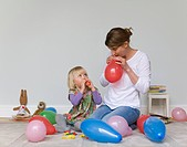 Woman and child blow up party balloons