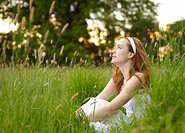 Woman sitting in countryside meadow.