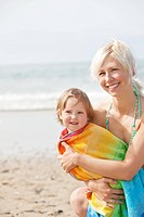 A cheerful girl in a towel and her smiling mother at the beach