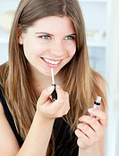 Smiling girl using lipstick at home