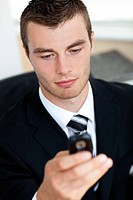 Concentrated young businessman sending a text sitting in his office