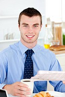 Happy businessman reading the newspaper drinking coffee in the morning at home in the kitchen