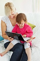 Mother and daughter having fun with a laptop in the living_room at home