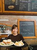 Woman holding tray of food in bakery