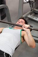 Muscular man working out with dumbbells in a fitness center
