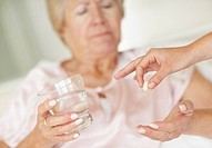 Nurse giving pill to senior woman