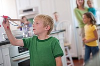 Young boy playing with toy airplane in kitchen