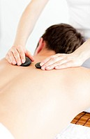 Caucasian young man receiving a back massage with hot stone in a spa center