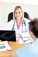 Smiling female doctor using her laptop and talking to her male patient in her office