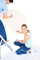 Serious caucasian couple painting a room in their new house