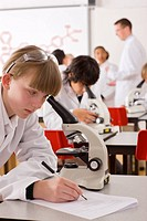 Students looking into microscopes in school laboratory