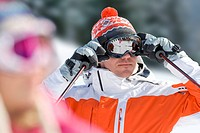 Serious skier adjusting goggles