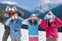 Family standing on ski slope with snowballs covering their eyes