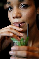 Woman drinking on a cocktail in a bar