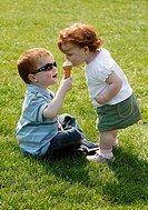 Two children sharing an ice cream in a park