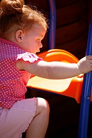 Baby girl with red hair playing outside