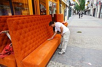 Man cleaning furniture on the street, Utrecht, The Netherlands