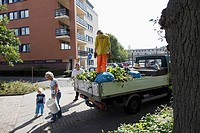 Woman with child give their garden waste to some gardener, Leusden, Utrecht province, Netherlands