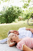 Mature couple cuddling on picnic blanket