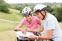 Mature cyclists looking at map in park