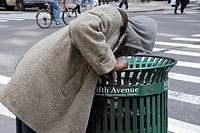 Homeless person looking in a bin at the 5th Avenue recyclable materials