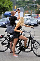 Couple cycling and taking pictures around the area of the Columbus monument, Ciutat Vella, Barcelona, Catalonia, Spain