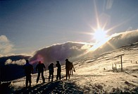 Group of skiers seen against setting sun and mountain slopes