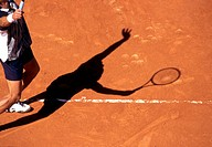 Tennis player serves on a clay court tennis court