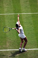 Woman serving on a grass tennis court