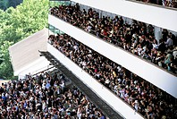 Crowded grandstand full of spectators at a horse racing meeting