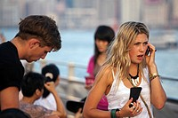 Tourist on phone, Victoria Harbour, Hong Kong, SAR, China