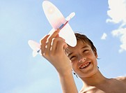 Young boy holding model airplane against blue sky
