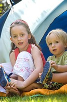 Portrait of boy and girl sitting by tent