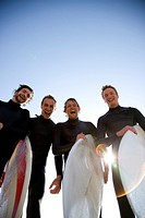 Surfers holding surfboards laughing and screaming