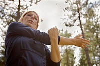Young woman standing in a forest stretching her arm