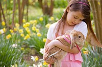 Close up of girl holding a lop-eared rabbit in a field of daffodils