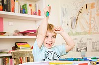 Smiling boy holding coloring pens above his head