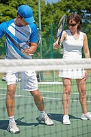 Tennis teacher instructing a woman