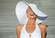 Close up of a young woman wearing a white hat laughing