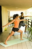 Mixed Ethnic couple doing yoga together at home